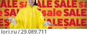 Купить «Composite image of woman in yellow raincoat gesturing to feel the rain», фото № 29089711, снято 24 октября 2018 г. (c) Wavebreak Media / Фотобанк Лори
