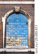 Купить «Old classic arched window in dark brick wall», фото № 29089811, снято 29 октября 2017 г. (c) EugeneSergeev / Фотобанк Лори