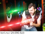 Купить «Emotional guy playing laser tag in colorful beams», фото № 29090923, снято 25 апреля 2018 г. (c) Яков Филимонов / Фотобанк Лори