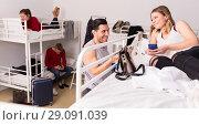 Hispanic traveler talking to girl in hostel bedroom. Стоковое фото, фотограф Яков Филимонов / Фотобанк Лори