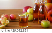 Купить «glass and bottles of apple juice on wooden table», видеоролик № 29092851, снято 7 сентября 2018 г. (c) Syda Productions / Фотобанк Лори