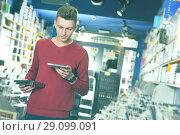 Купить «guy looking on box of DVD movie», фото № 29099091, снято 15 февраля 2018 г. (c) Яков Филимонов / Фотобанк Лори
