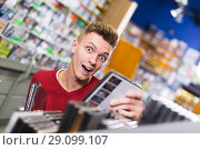 Купить «Surprised guy choosing DVD», фото № 29099107, снято 15 февраля 2018 г. (c) Яков Филимонов / Фотобанк Лори