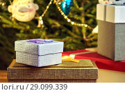 Купить «Gift boxes with bows on the lids under a Christmas tree in New Year Eve», фото № 29099339, снято 1 января 2018 г. (c) Георгий Дзюра / Фотобанк Лори