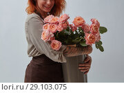 Купить «Smiling girl in a brown apron with a tattoo holds a beautiful bouquet of pink roses in a vase on a gray background with space for text. The concept of Valentine's Day.», фото № 29103075, снято 3 декабря 2017 г. (c) Ярослав Данильченко / Фотобанк Лори
