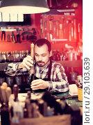 Купить «Male worker working on leather for belt in leather», фото № 29103639, снято 21 октября 2018 г. (c) Яков Филимонов / Фотобанк Лори