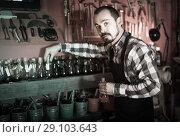 Купить «man worker examining colorants for leather in leather workshop», фото № 29103643, снято 19 октября 2018 г. (c) Яков Филимонов / Фотобанк Лори