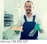 Купить «Young man in apron cleaning shelves», фото № 29103727, снято 20 июня 2019 г. (c) Яков Филимонов / Фотобанк Лори