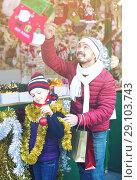 Купить «Man with daughter choosing presents in Christmas market», фото № 29103743, снято 20 сентября 2018 г. (c) Яков Филимонов / Фотобанк Лори