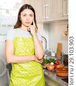 Купить «Young girl housewife in apron looking tired at kitchen», фото № 29103903, снято 18 апреля 2018 г. (c) Яков Филимонов / Фотобанк Лори