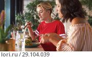 Купить «female friends eating at restaurant», видеоролик № 29104039, снято 23 августа 2018 г. (c) Syda Productions / Фотобанк Лори