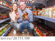 Family couple holding pickle goods in the hypermarket. Стоковое фото, фотограф Яков Филимонов / Фотобанк Лори