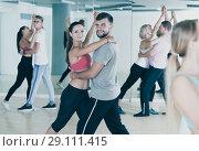 Купить «smiling young adults dancing salsa», фото № 29111415, снято 9 октября 2017 г. (c) Яков Филимонов / Фотобанк Лори