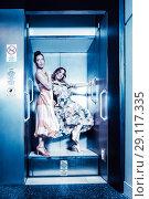 Купить «Dark color toned picture of two fashionable sexy girl in the elevator», фото № 29117335, снято 22 ноября 2019 г. (c) Игорь Бородин / Фотобанк Лори