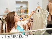 Купить «woman choosing clothes at clothing store», фото № 29123447, снято 19 февраля 2016 г. (c) Syda Productions / Фотобанк Лори
