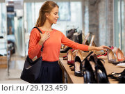 Купить «happy young woman choosing shoes at store», фото № 29123459, снято 22 сентября 2017 г. (c) Syda Productions / Фотобанк Лори