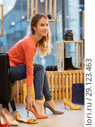 Купить «young woman trying high heeled shoes at store», фото № 29123463, снято 22 сентября 2017 г. (c) Syda Productions / Фотобанк Лори