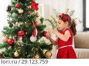 Купить «little girl decorating christmas tree at home», фото № 29123759, снято 29 августа 2018 г. (c) Syda Productions / Фотобанк Лори