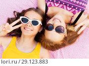 Купить «teenage girls in sunglasses showing peace sign», фото № 29123883, снято 19 июля 2018 г. (c) Syda Productions / Фотобанк Лори