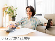 Купить «woman with tablet pc, bills and calculator at home», фото № 29123899, снято 12 мая 2018 г. (c) Syda Productions / Фотобанк Лори