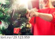 Купить «close up of senior woman decorating christmas tree», фото № 29123959, снято 14 сентября 2017 г. (c) Syda Productions / Фотобанк Лори