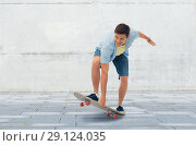 Купить «young man riding skateboard over urban background», фото № 29124035, снято 30 июня 2018 г. (c) Syda Productions / Фотобанк Лори