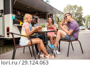 Купить «happy friends with drinks eating at food truck», фото № 29124063, снято 1 августа 2017 г. (c) Syda Productions / Фотобанк Лори