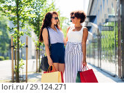 Купить «happy women with shopping bags in city», фото № 29124271, снято 22 июля 2018 г. (c) Syda Productions / Фотобанк Лори