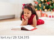 Купить «happy girl reading book at home on christmas», фото № 29124315, снято 29 августа 2018 г. (c) Syda Productions / Фотобанк Лори