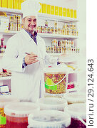 Купить «Shop staff standing near containers with olives in flavoured brine», фото № 29124643, снято 15 октября 2016 г. (c) Яков Филимонов / Фотобанк Лори