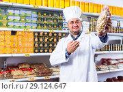 Купить «Salesman standing in food shop», фото № 29124647, снято 15 октября 2016 г. (c) Яков Филимонов / Фотобанк Лори