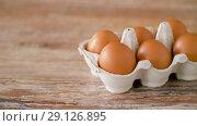 Купить «close up of eggs in cardboard box on wooden table», видеоролик № 29126895, снято 21 августа 2018 г. (c) Syda Productions / Фотобанк Лори
