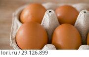 Купить «close up of eggs in cardboard box on wooden table», видеоролик № 29126899, снято 21 августа 2018 г. (c) Syda Productions / Фотобанк Лори