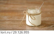 Купить «yogurt or sour cream in glass jar on wooden table», видеоролик № 29126955, снято 21 августа 2018 г. (c) Syda Productions / Фотобанк Лори