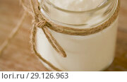 Купить «yogurt or sour cream in glass jar on wooden table», видеоролик № 29126963, снято 21 августа 2018 г. (c) Syda Productions / Фотобанк Лори