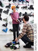 Купить «Man seller assisting boy in trying on roller-skates», фото № 29128031, снято 21 декабря 2016 г. (c) Яков Филимонов / Фотобанк Лори