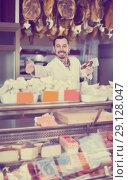 Купить «Positive man butcher showing sorts of meat», фото № 29128047, снято 2 января 2017 г. (c) Яков Филимонов / Фотобанк Лори