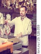 Купить «Positive male seller weighing on scales sausage», фото № 29128059, снято 2 января 2017 г. (c) Яков Филимонов / Фотобанк Лори