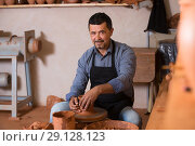 Купить «Male working with clay on pottery wheel», фото № 29128123, снято 22 октября 2018 г. (c) Яков Филимонов / Фотобанк Лори