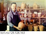 Купить «mature man potter holding ceramic vessels», фото № 29128163, снято 6 декабря 2019 г. (c) Яков Филимонов / Фотобанк Лори