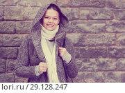 Купить «cheerful female in coat hood near wall», фото № 29128247, снято 11 ноября 2017 г. (c) Яков Филимонов / Фотобанк Лори