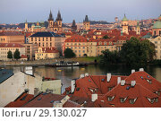 Купить «Prague, Czech Republic, September 19, 2018. Beautiful view from above on the city, red roofs of houses, the Vltava River and the Church of the Virgin Mary», фото № 29130027, снято 19 сентября 2018 г. (c) Яна Королёва / Фотобанк Лори