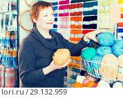 Купить «Mature woman choosing colorful yarn in shop», фото № 29132959, снято 10 мая 2017 г. (c) Яков Филимонов / Фотобанк Лори