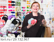 Купить «Mature woman is standing in needlework store», фото № 29132967, снято 10 мая 2017 г. (c) Яков Филимонов / Фотобанк Лори