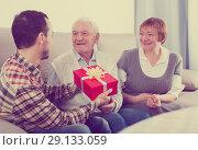 Купить «Son gives gift to parents», фото № 29133059, снято 19 марта 2019 г. (c) Яков Филимонов / Фотобанк Лори