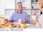 Купить «Wife treats husband with tasty pastries at table at home», фото № 29133255, снято 26 июня 2019 г. (c) Яков Филимонов / Фотобанк Лори
