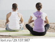 Купить «Cross-legged couple practice yoga on beach in morning», фото № 29137987, снято 22 октября 2018 г. (c) Яков Филимонов / Фотобанк Лори