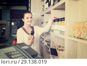 Купить «Young female customer examining various juices», фото № 29138019, снято 23 ноября 2016 г. (c) Яков Филимонов / Фотобанк Лори