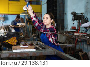 Купить «Girl worker is holding lift hook equipment in workshop.», фото № 29138131, снято 10 октября 2017 г. (c) Яков Филимонов / Фотобанк Лори