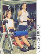 Купить «Woman making leg extension exercise using gym machinery», фото № 29138167, снято 4 октября 2016 г. (c) Яков Филимонов / Фотобанк Лори